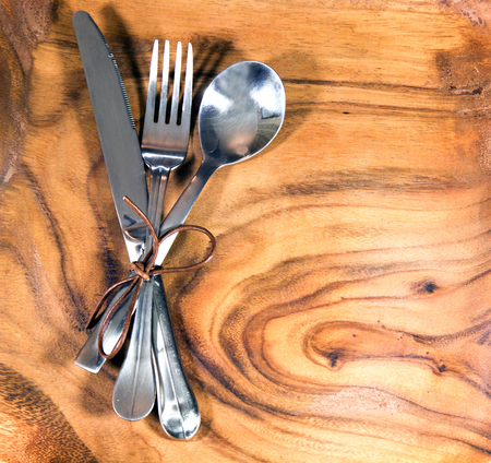 Set of fork, spoon and knife on wooden table Stock Photo
