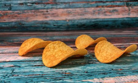 Crispy thin potato chips on a blue background