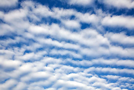 Beautiful fluffy white clouds on blue sunny sky as background