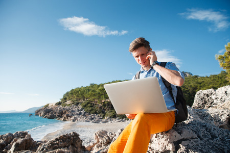 Handsome young male businessman working on the laptop by the seaside