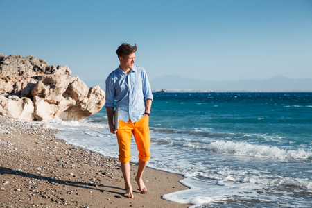 barefooted: Handsome young barefooted man walking with laptop at the coast Stock Photo