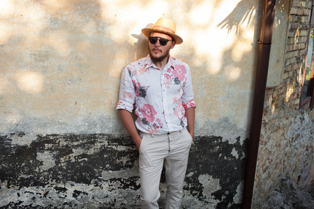 only man: Male tourist in small summer town wearing bright shirt, hat and sunglasses getting rest and relax Stock Photo