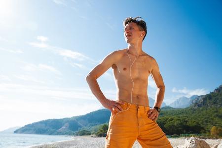 harsh light: Extreme seaside sport man running on the water at sunrise harsh light