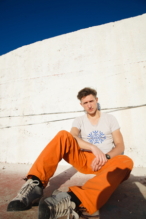 Young man getting rest and relax on the sidewalks over the sea, blue sky and palms