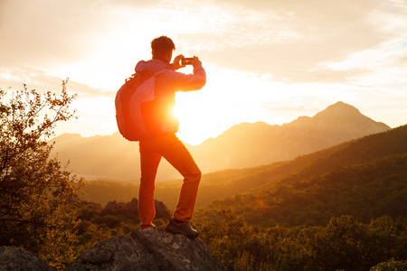 outdoor sport: Hiker with backpack stands on che rock cliff in the mountains over the rising sun