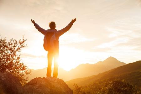 słońce: Turysta z plecakiem stoi na che skale, wznoszącej się w górach nad wschodzącego słońca