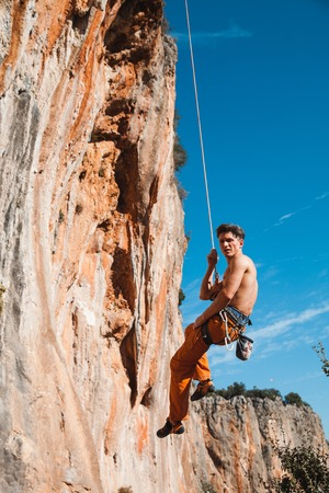 belay: Handsome adult male rock climber hanging on belay rope over the blue sky and mountains. Turkey, Geyikbayiri - Stock Image