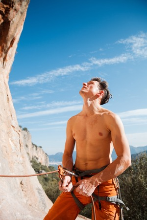 belay: Handsome adult male rock climber holding belay rope over the blue sky and mountains. Turkey, Geyikbayiri - Stock Image Stock Photo
