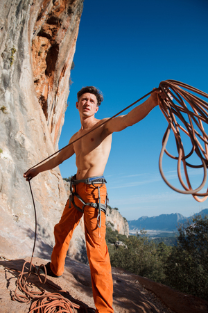 belay: Handsome adult male rock climber collecting the belay rope over the blue sky and mountains. Turkey, Geyikbayiri - Stock Image
