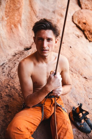 belay: Handsome adult male rock climber holding belay rope against the rock mountains, portrait, close-up, stock Image Stock Photo