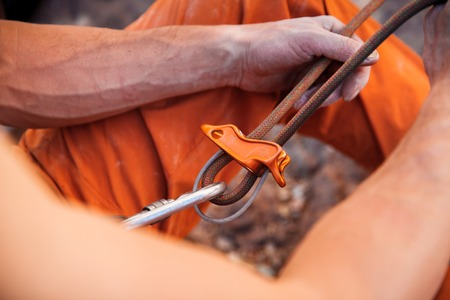 belay: Handsome adult male rock climber holding belay rope - hands closeap. Turkey, Geyikbayiri - Stock Image