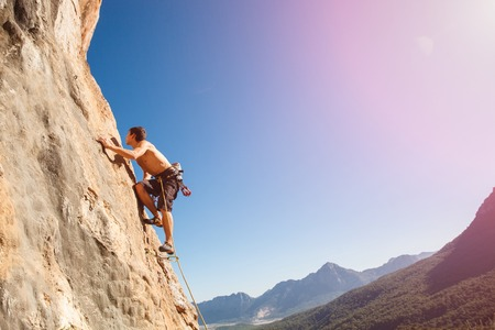 belay: Male rock climber on the wall against the blue sky and mountains - stock photo. Stock Photo
