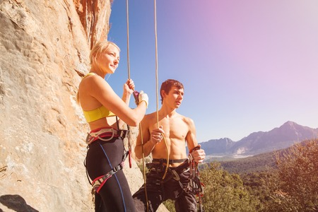 climbers: Couple of rock climbers - woman holding man with belay rope against the blue sky and mountains. Stock photo.