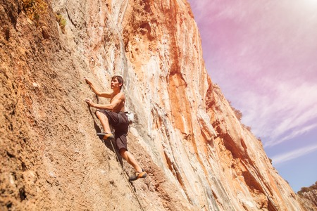 rock climber: Male rock climber on the wall against the blue sky and mountains - stock photo. Stock Photo