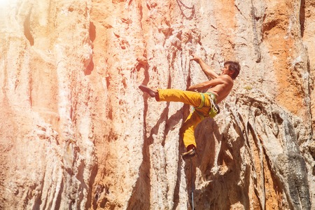 belay: Mature mrock climber on the wall against the blue sky and mountains - stock photo. Stock Photo