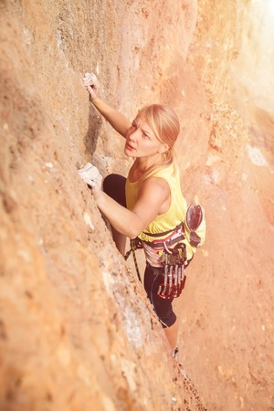 belay: Female rock climber on the wall - top view against the mountains - stock photo.
