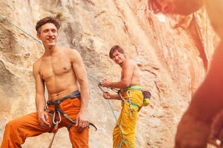 belay: Two rock climbers with belay rope on the cliff against blue sky and mountains. Stock image.