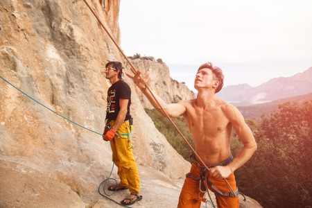 Two rock climbers with belay rope on the cliff against blue sky and mountains. Stock image.