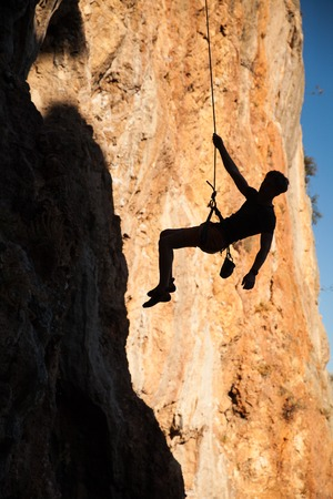 belay: Silhouette of adult male rock climber hanging on belay rope against the blue sky and mountains - stock image Stock Photo
