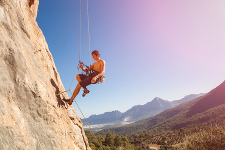 mountain top: Male rock climber on belay rope against the blue sky and mountains - stock photo.