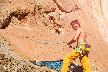 belay: Rock climber with belay rope and glasses on the cliff against blue sky and mountains. Stock image. Stock Photo