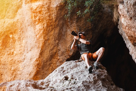 man looking at sky: Male photographer on the cliff in the cage shooting on dslr camera. Concept of freelance working - stock image Stock Photo
