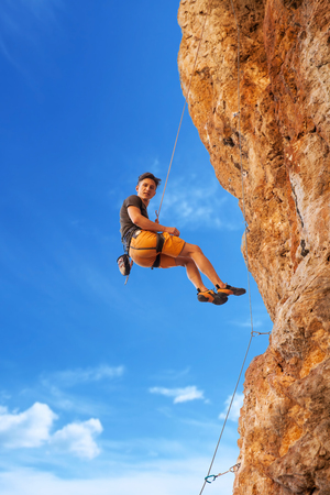 belay: Adult male rock climber hanging on belay rope against the blue sky and mountains - stock image Stock Photo