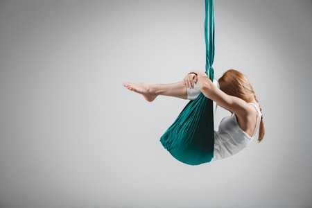 aerial: An adult woman practices different inversion - anti-gravity yoga positions in a bright well lit studio.