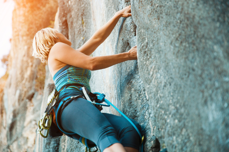 only one person: Adult female rock climber on vertical flat wall with poor relief - side view, close-up. Stock Photo