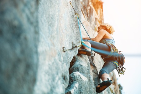 Adult female rock climber on vertical flat wall with poor relief - side view, close-up. Stock Photo