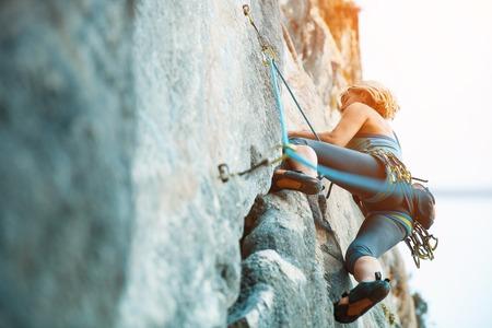Adulto hembra escalador en la pared plana vertical con la ayuda pobre - vista lateral, primer plano. Foto de archivo
