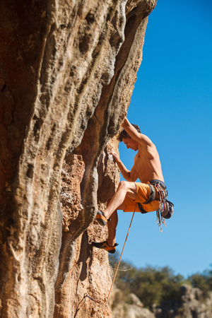 adrenaline rush: Rebelious rock climber on the wall against the blue sky - bold choice of real men. Dangerous adventure. Turkey, Geyikbayiri - Stock Image, Close-Up