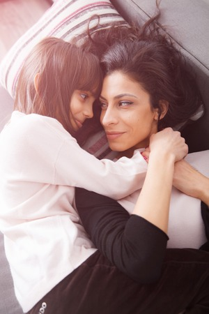 20 29: Young mother and her daughther laying on the sofa and hugging at home in white lit room against the window. Smooth morning light, casual style - concept of happy family living and lifestyle