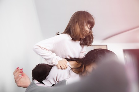 20 29: Young woman piggybacking her joyful little daughter at home in white lit room against the window. Smooth morning light, casual style - concept of happy family living and lifestyle Stock Photo