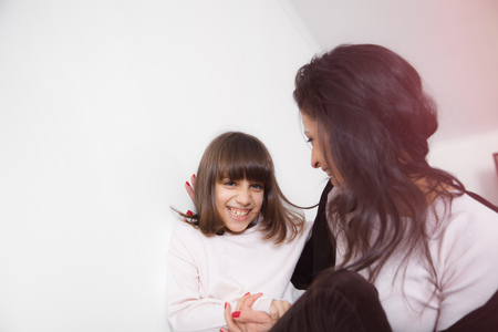 20 29: Young mother and daughter having fun, kiss and hugs on the sofa at home in white lit room against the window. Smooth morning light, casual style - concept of happy family living and lifestyle Stock Photo