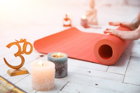 spiritual woman: Woman hands roll up red gymnastic carpet in white lit room with spiritual accessories