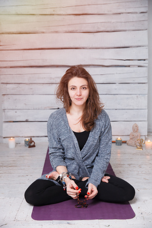 meditation room: Handsome woman having yoga meditation on violet gymnastic carpet in white lit room with candles. She has long hair, black sport suit and ethnic accessories.