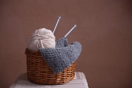 purl: Basket witn yarn ball, knitting and needles. Close-up horiaontal photo. Freelance creative working and living concept