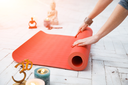 om sign: Woman hands roll up red gymnastic carpet in white lit room with spiritual accessories