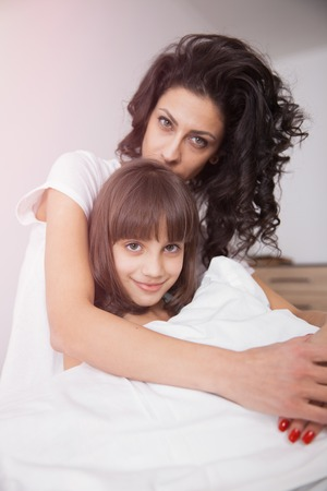 daugther: Brunette long hair mother and daugther hugging on the bed. Concept of happy family living, relaxation, comfort, fun