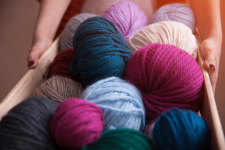 purl: Woman holding a basket with colorful yarn ball and knitting needles. Close-up vertical photo. Freelance creative working and living concept