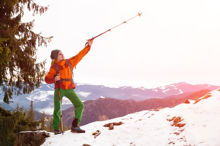 trekking pole: Male hiker in winter mountains against blue sky pointing on horizon with trekking pole. Concept of success living and free traveling, active leisure, health care and well being. Stock Photo