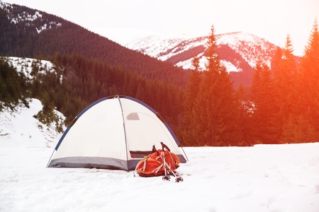 living being: Tent with backpack in winter mountains. Concept of success living and free traveling, active leisure, health care and well being.