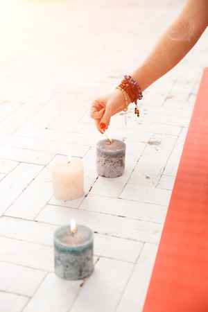 horisontal: Spiritual accessories, candles, statues and yoga relaxation in white lit room. Concept of physical and mental health, happy living and wellbeing.
