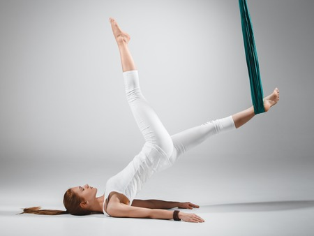 An adult woman practices different inversion - anti-gravity yoga positions in a bright well lit studio. Фото со стока - 56420181