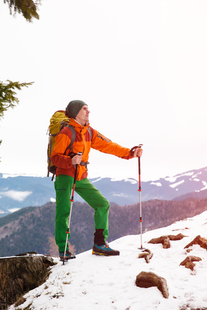 trekking pole: Male hiker in winter mountains against blue sky with trekking pole. Concept of success living and free traveling, active leisure, health care and well being.