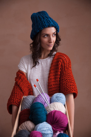 purl: Young smiling woman in knitted clothes holding a wooden box witn colorful yarn clews and knitting needles. Concept of freelance creative working and living