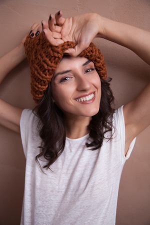 purl: Young smiling happy woman in knitted  hat. Concept of freelance creative working and happy living