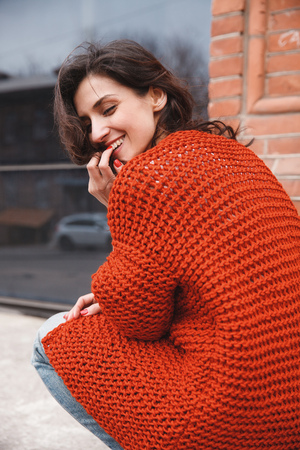 purl: Portrait of young woman wearing colorful knitted clothes. Outdoor, street, lifestyle. Concept of freelance creative working and living.