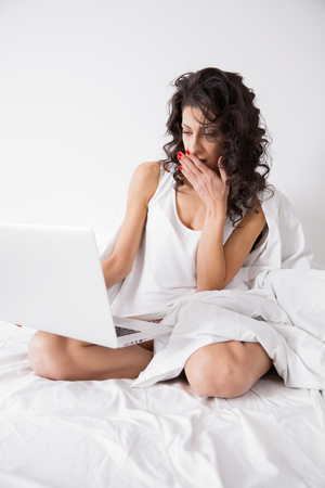 internet surfing: Brunette long hair woman on white bed in soft morning light under the duvet with a laptop computer. Concept of happy family living, relaxation, comfort, fun, internet surfing and communicating Stock Photo